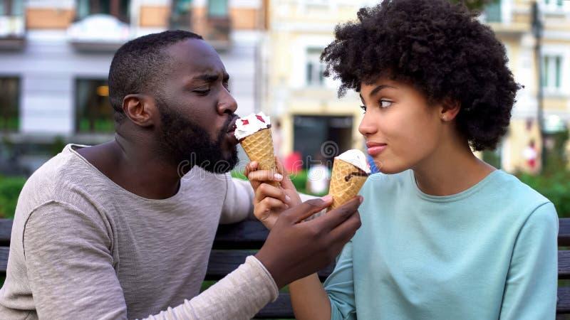 Ame os sócios que compartilham do gelado durante a data no parque da cidade, divertimento do verão junto fotografia de stock royalty free