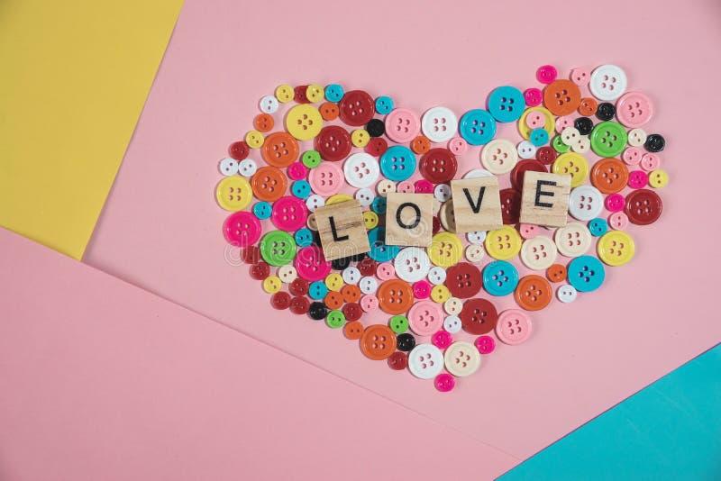 Ame a palavra escrita no bloco de madeira colocado no botão colorido dentro fotos de stock royalty free