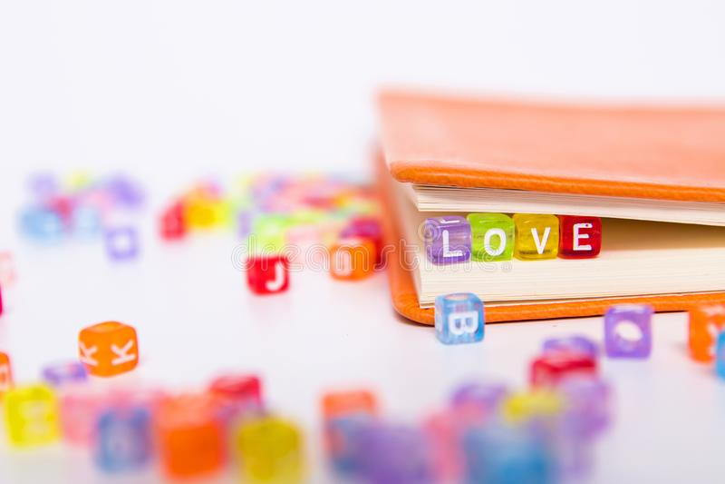 AME a palavra no bloco colorido do gr?nulo como o marcador no livro Conceito da fic??o da hist?ria de amor imagens de stock