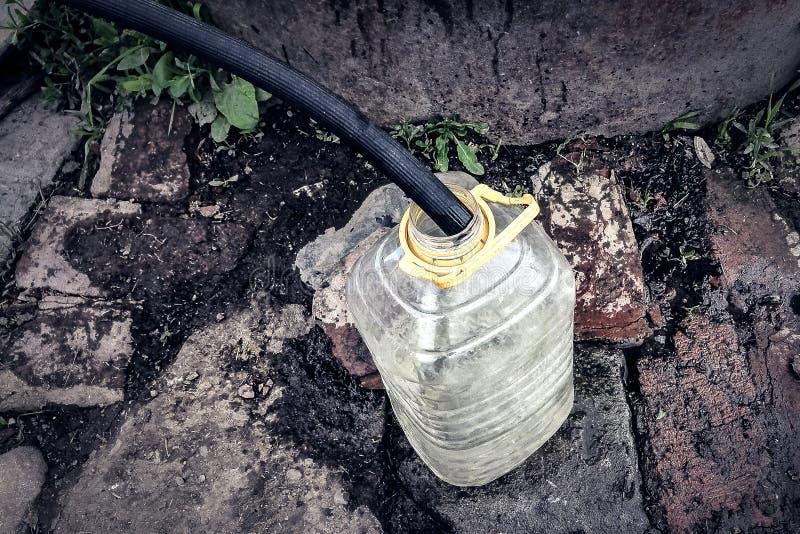 Ameaças da falta e das alterações climáticas da fonte de água: recolhendo a água potável com a garrafa de água plástica de 5 litr fotos de stock royalty free