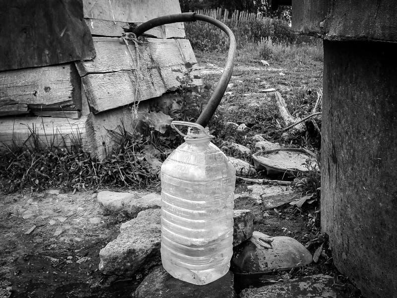 Ameaças da falta e das alterações climáticas da fonte de água: recolhendo a água potável com a garrafa de água plástica de 5 litr imagens de stock royalty free