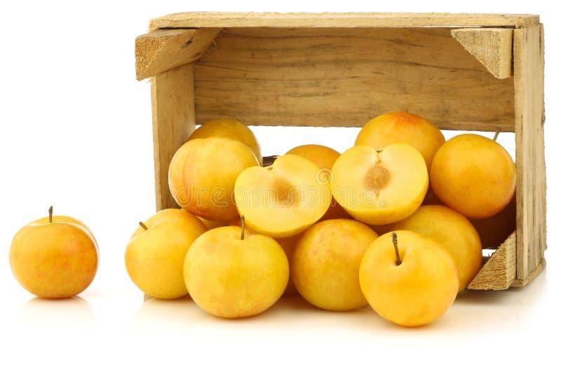 Ameixas amarelas e um corte uma em uma caixa de madeira imagem de stock
