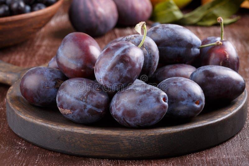 Ameixas de ameixa roxas inteiras maduras frescas na placa de madeira imagem de stock