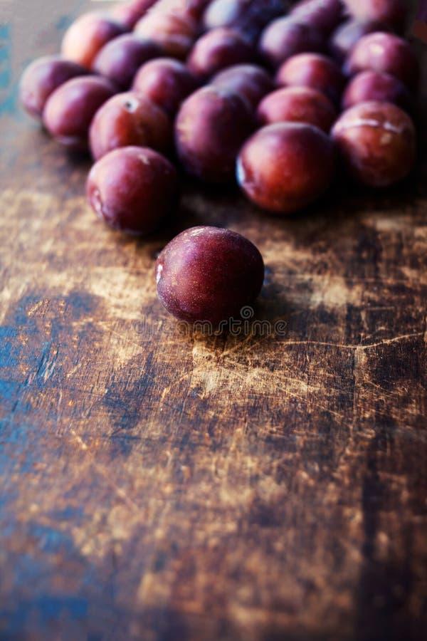 Ameixas frescas em uma tabela de madeira escura Textura madura das ameixas sobre o vint foto de stock royalty free