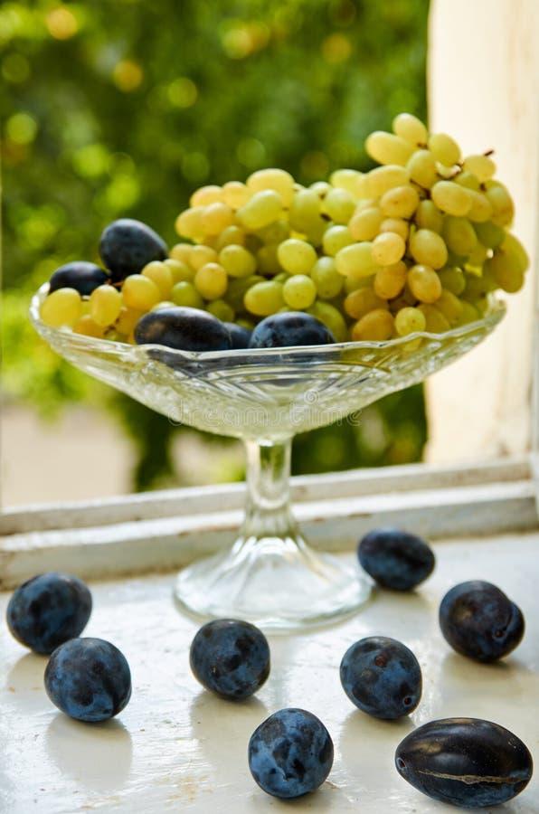 Ameixas frescas no fim velho branco da superfície acima As uvas e as ameixas verdes no suporte de fruto de vidro na natureza verd fotos de stock royalty free