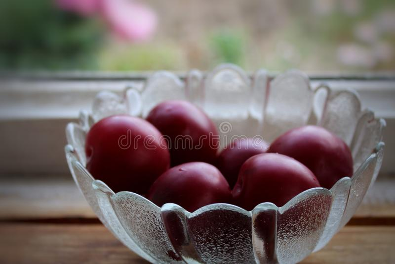 Ameixas maduras em uma bacia de cristal no fundo de madeira fotos de stock royalty free