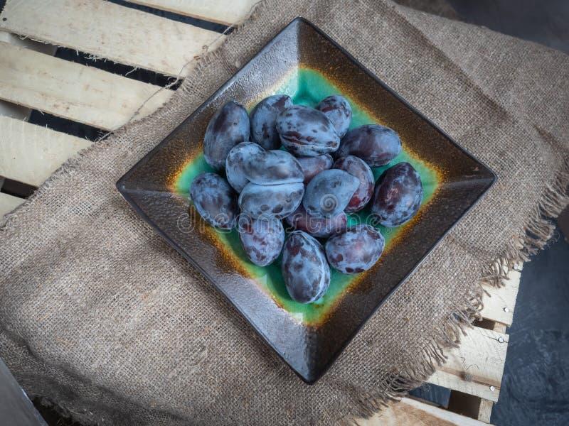 Ameixas secas frescas em uma placa em um revestimento protetor de serapilheira e em uma caixa de madeira das venezianas fotografia de stock