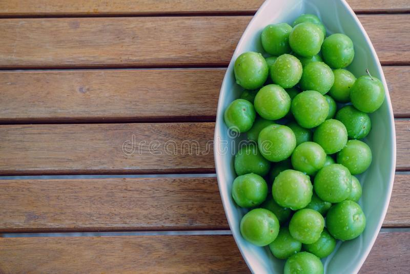 Ameixas verdes no prato branco no fim de madeira do fundo acima da vista com copyspace fotos de stock