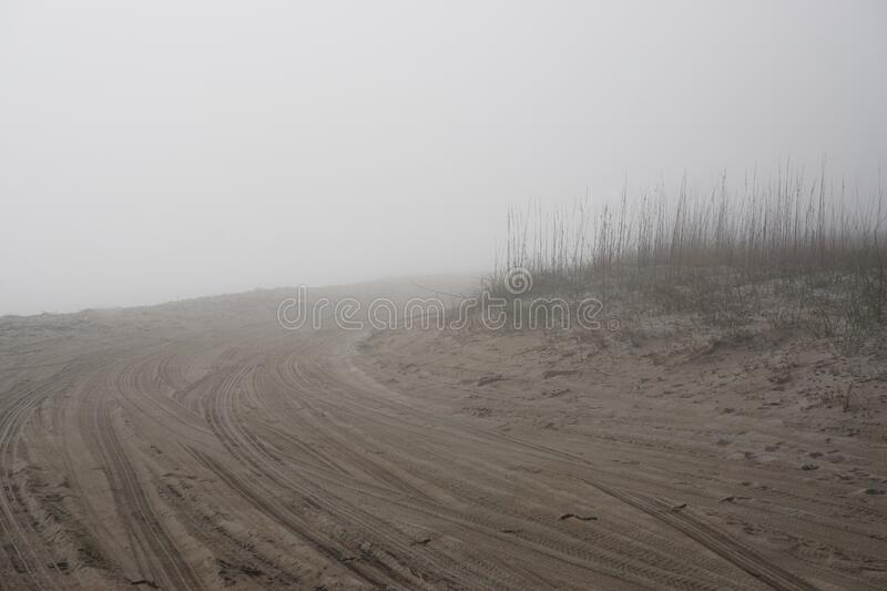 Amelia Island, Florida, USA: Tire tracks in the sand at mist-covered American Beach royalty free stock photography
