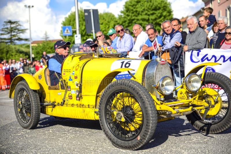 Amelia Italien, Maj 2018 Mille Miglia 1000 mil, historisk tappningbiltävling Två män som kör en historiska Bugatti, gul färg royaltyfri fotografi