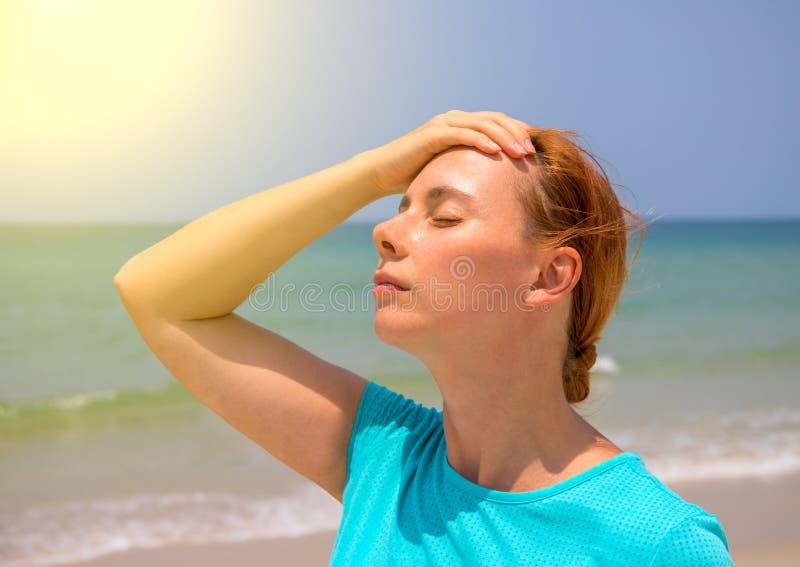 Amenaza tropical del sol de la playa para la salud Mujer en la playa caliente con la insolación Problema de salud el día de fiest fotos de archivo