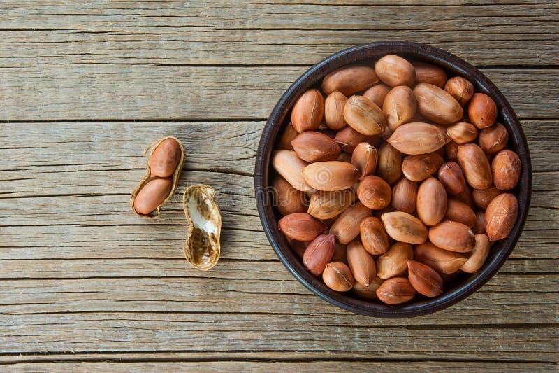 Amendoim na casca de noz na bacia marrom no fundo de madeira composição dos amendoins fotografia de stock royalty free