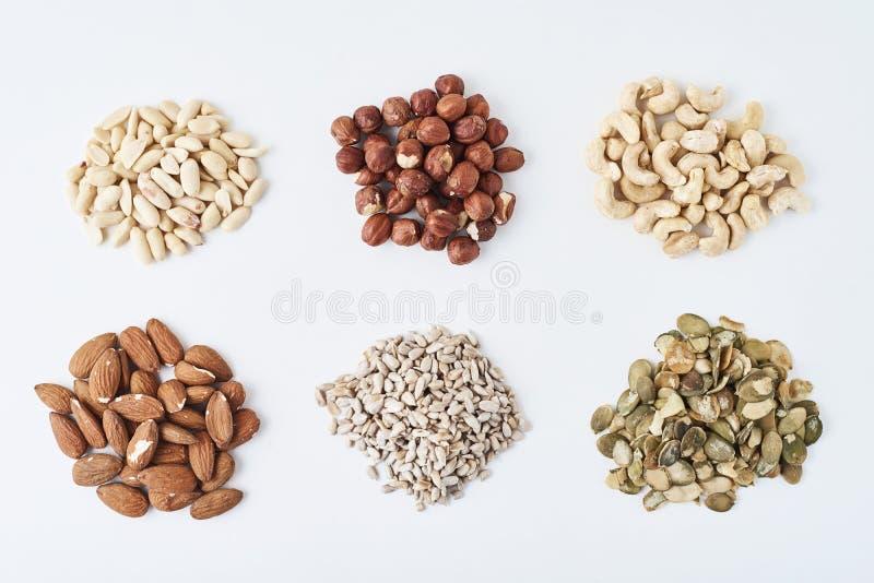 Amendoins, cajus, avelã, amêndoas, sementes de abóbora e sementes de girassol em um fundo isolado branco imagens de stock royalty free