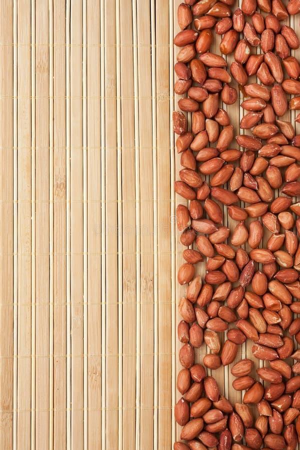 Amendoins descascados que encontram-se em uma esteira de bambu imagem de stock
