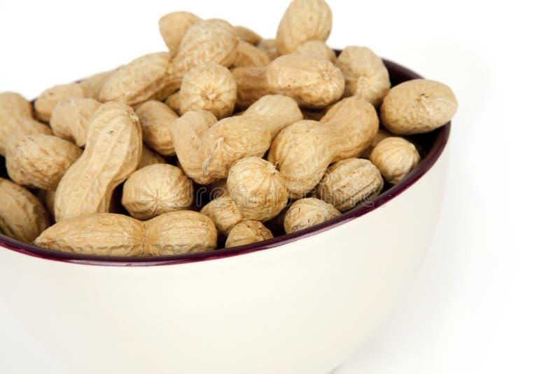 Amendoins em uma bacia cerâmica em um fundo branco imagens de stock royalty free