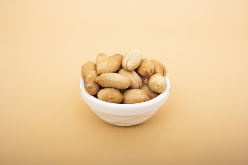 Amendoins no porchelain branco, amendoins no fundo amarelo isolado foto de stock