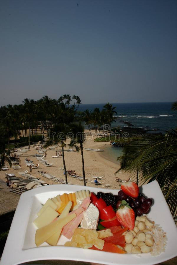 Display of assorted fruits, cheese and nuts on a white plate with a tropical beach in the background. Amenity plate of assorted fruits, cheese and nuts set on a royalty free stock image