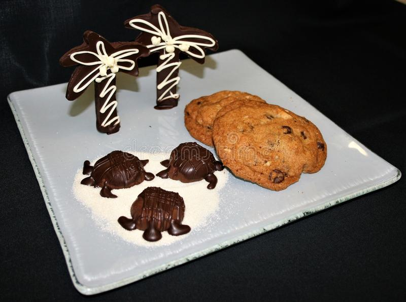 Display of Chocolate turtles and palm trees on a sugar beach with assorted cookies on a white plate and black background stock photography
