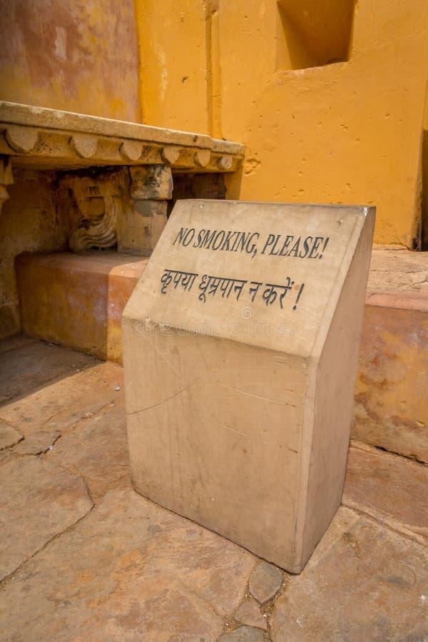 Amer Indien - September 19, 2017: Informativt tecken av att inte röka i en asfull struktur i den Amber Fort slotten som in lokali arkivfoto
