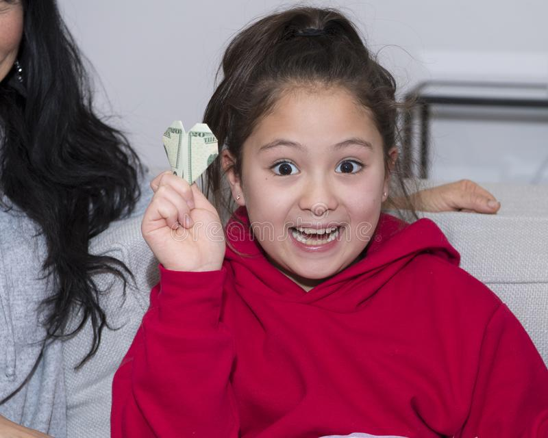 Amerasian girl enthusiastic about her Christmas gift, a twenty dollar bill made into a heart through oragami royalty free stock photography