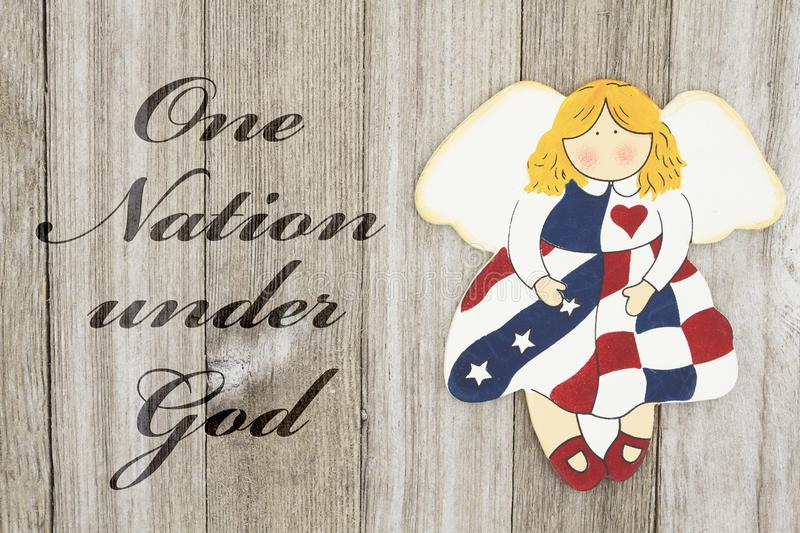 America patriotic message. USA patriotic old flag on an angel and weathered wood background with text One Nation Under God stock image