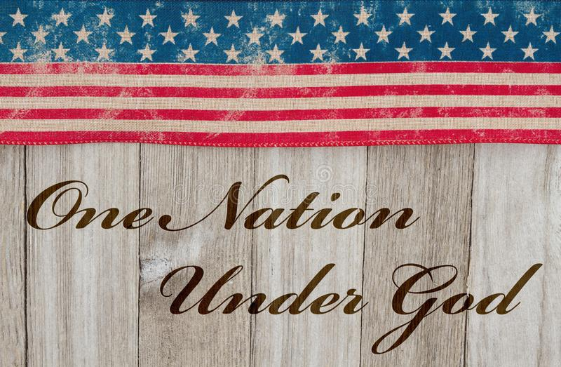 America patriotic message one nation under God. America patriotic message, USA patriotic old flag and weathered wood background with text One Nation Under God royalty free stock photos