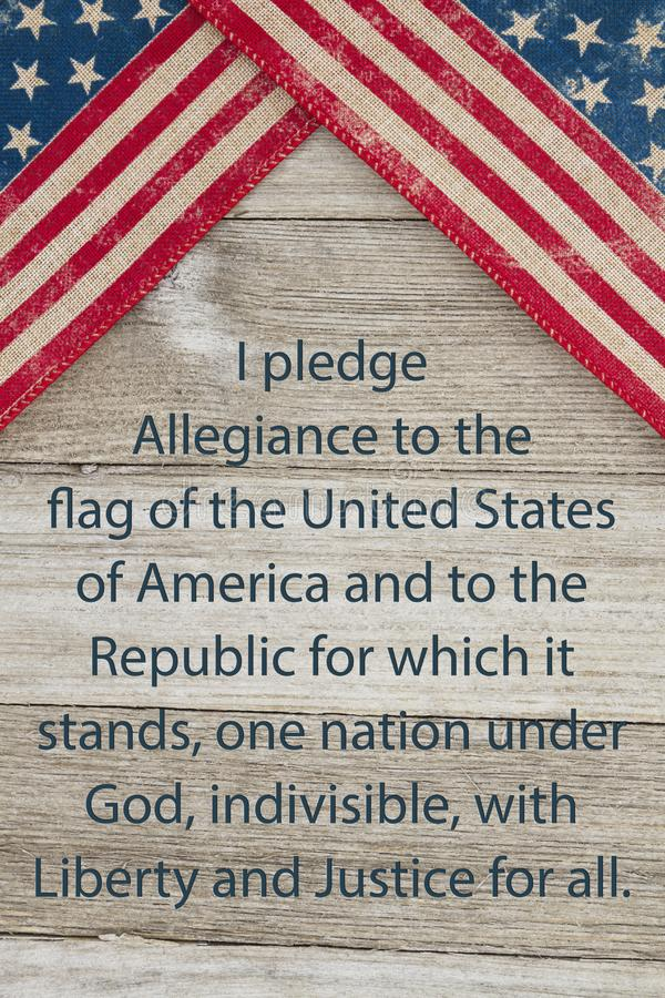 America patriotic message. USA patriotic old flag and weathered wood background with text of the Pledge of Allegiance stock photography