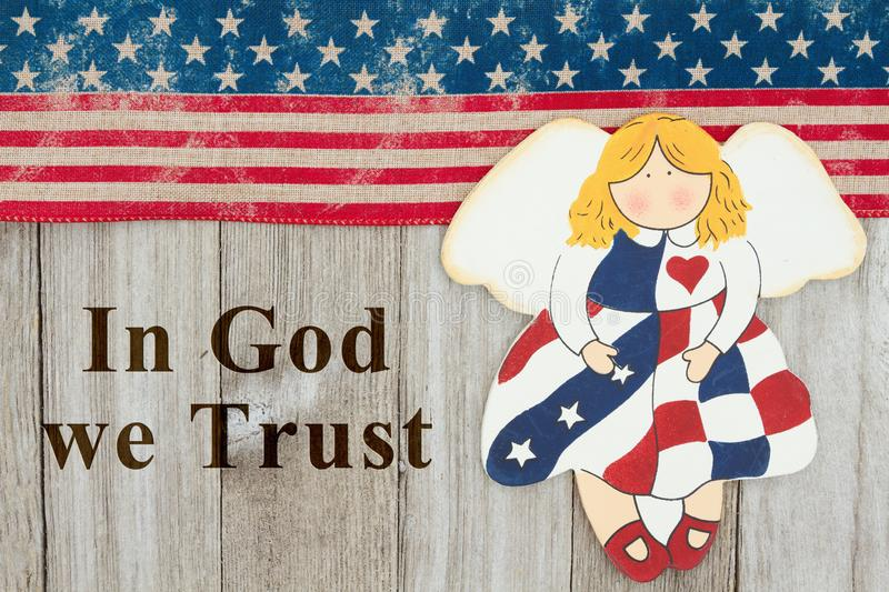 America patriotic message. USA patriotic old flag and an angel and weathered wood background with text In God we Trust stock images
