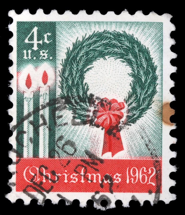 America`s first Christmas postage stamp shows a wreath and candles royalty free stock photo