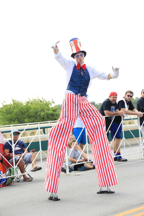 American Independence Day parade. America's Independence parade. The man dressed in a colorful costume walking on stilts in the main street of Round Rock stock photography