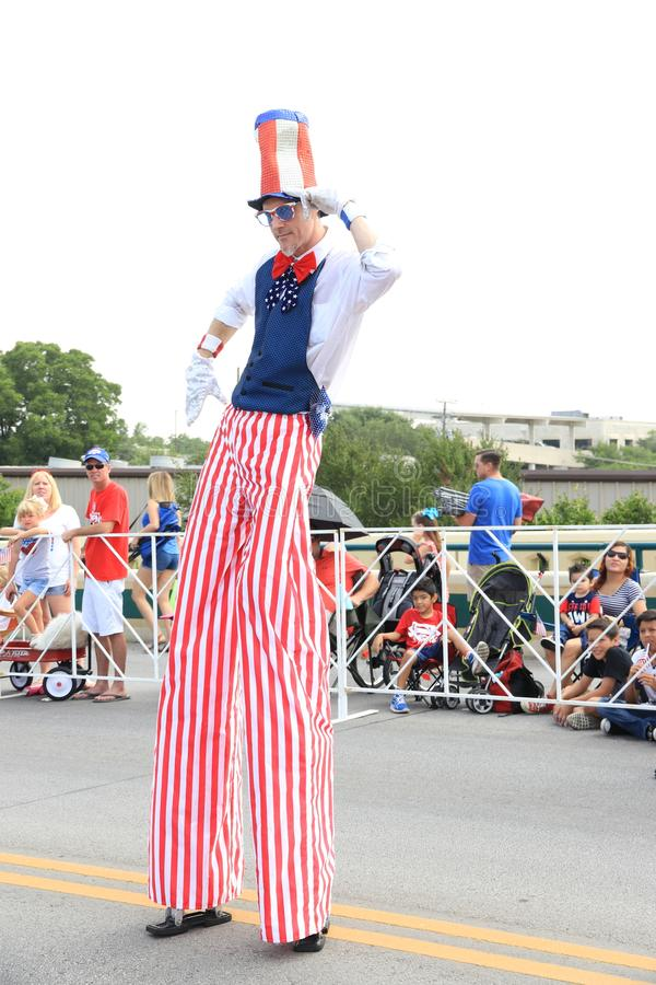 American Independence Day parade. America's Independence parade. The man dressed in a colorful costume walking on stilts in the main street of Round Rock stock images