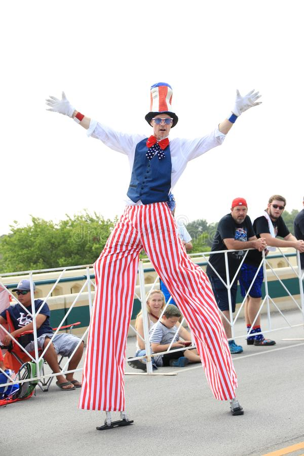 American Independence Day parade. America's Independence parade. The man dressed in a colorful costume walking on stilts in the main street of Round Rock royalty free stock photography