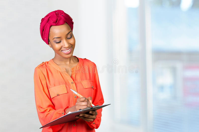 American african business woman with clipboard. Portrait of an attractive young american african business woman with clipboard stock photography