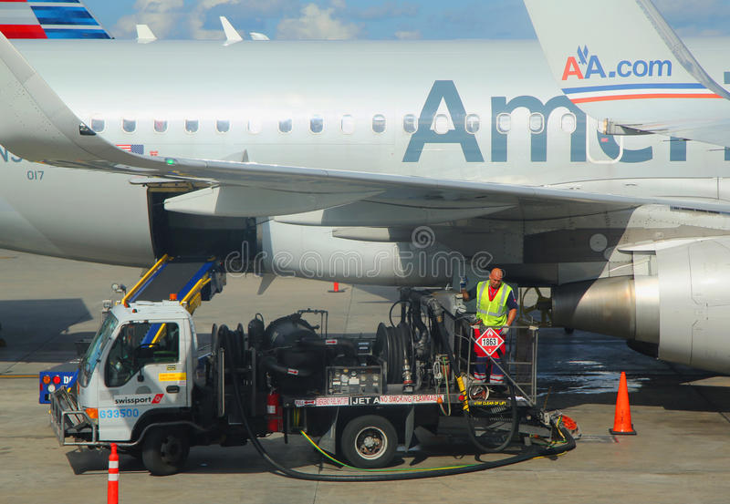 American Airlines worker refueling plane at Miami International Airport royalty free stock image