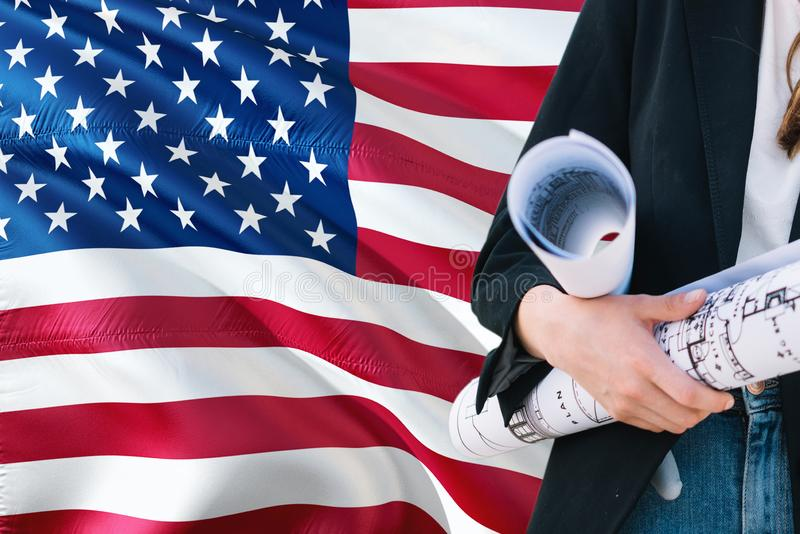 American Architect woman holding blueprint against United States of America waving flag background. Construction and architecture stock images