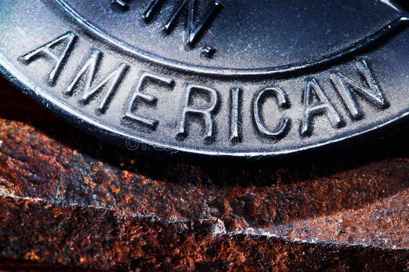 American as a Trademark Word Stamped in Iron. The trademark origin word American stamped in a cast iron tool over rusty steel background stock photography
