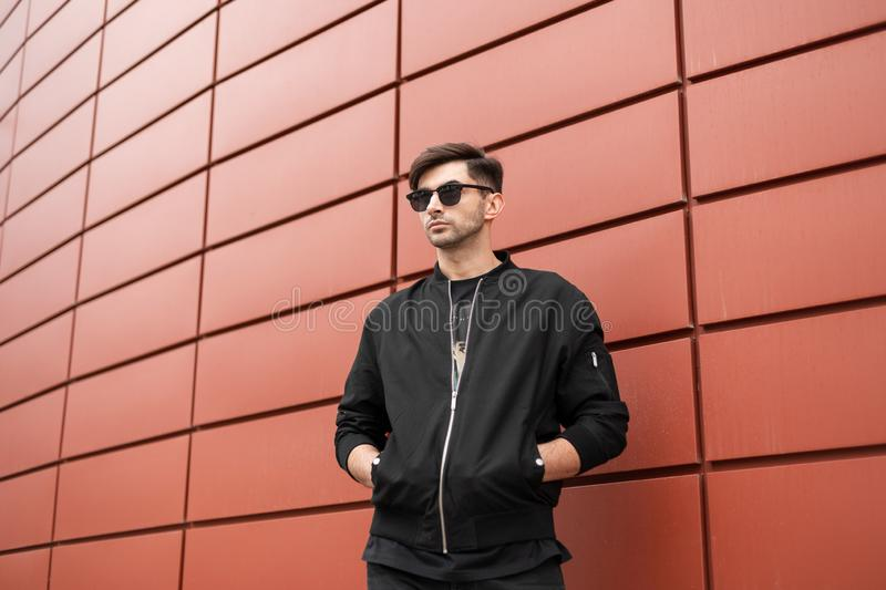 American attractive young hipster man with a fashionable hairstyle in stylish sunglasses in a vintage black jacket posing stock photography
