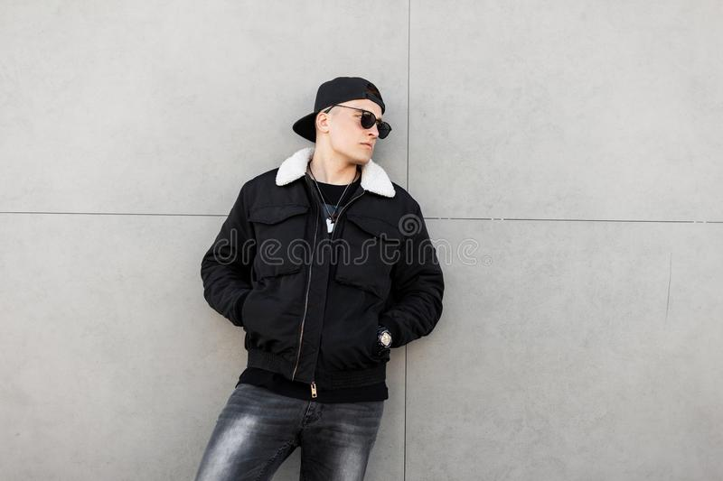 American attractive young man hipster in black fashionable jacket with white fur in dark sunglasses in a stylish baseball cap. In vintage jeans is resting near royalty free stock photo