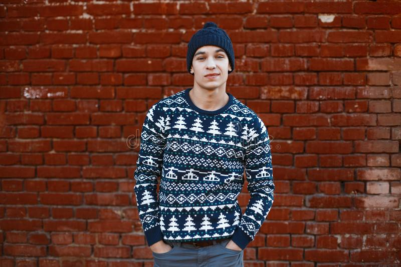American attractive young stylish man in a knitted blue sweater with a Christmas ornament in a winter blue knitted hat. In jeans posing outdoors near a vintage royalty free stock photography