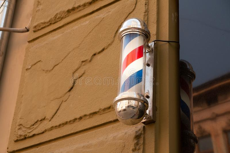 American barber pole sign with a helical stripe red, white, and blue on a wall royalty free stock photos