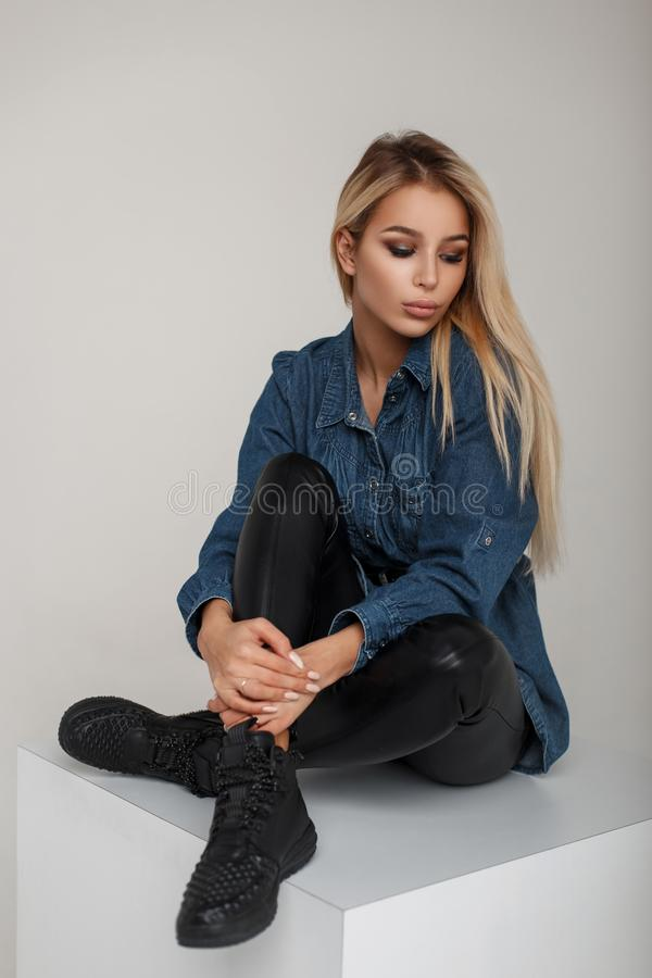 American beautiful young blonde woman in denim clothes with. Leather pants in stylish black sneakers sits in studio stock images