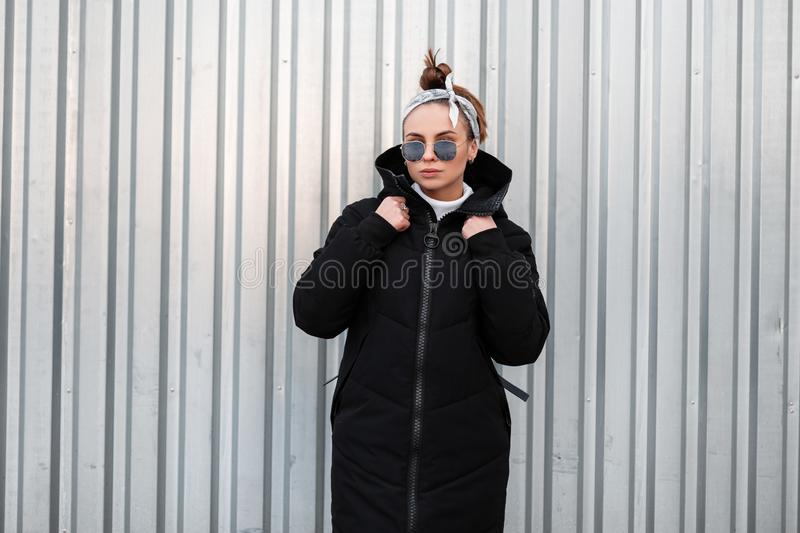 American beautiful young hipster woman in a winter stylish black coat with a leather backpack with a bandana in sunglasses. Near a metal building. Nice girl on royalty free stock images
