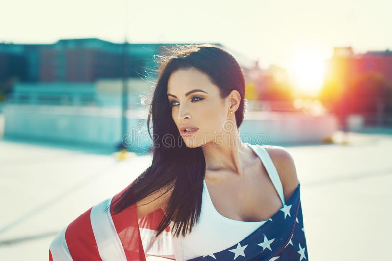 American beauty covered by star spangled banner in sunset. Portrait, looking away, Independence day, 4th of July royalty free stock photos