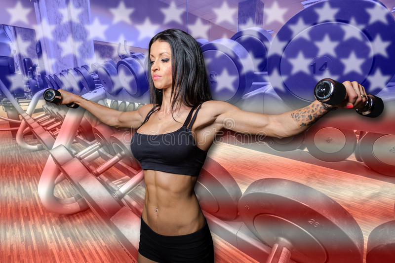 American bodybuilder. Woman bodybuilder with dumbbells on american flag in the gym royalty free stock photography