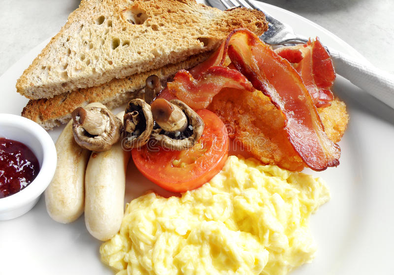 American breakfast. An image of a hearty American style breakfast with brown toasts, rasberry jam, bacon strips, sausages, scrambled eggs and tomato with stock photos