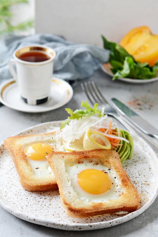 American breakfast on a plate with fried eggs in toast, with tomatoes, fresh daikon, carrots, arugula and espresso. Fried egg royalty free stock image