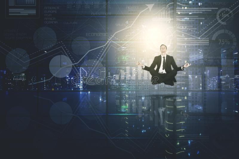American businessman meditating with growth graph. American businessman levitating in the office while meditating with growth graph background royalty free stock images