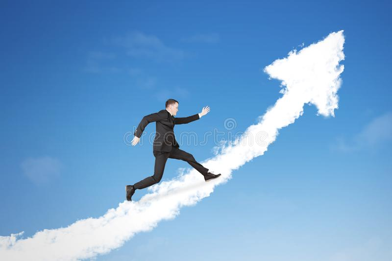 American businessman running above an upward arrow. American businessman wearing a formal suit while running above clouds shaped upward arrow in the blue sky royalty free stock photography