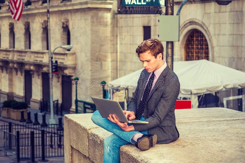 American businessman traveling, working in New York. Young blonde, handsome student, wearing blazer, necktie, jeans, crossing legs, reading, working on laptop stock image