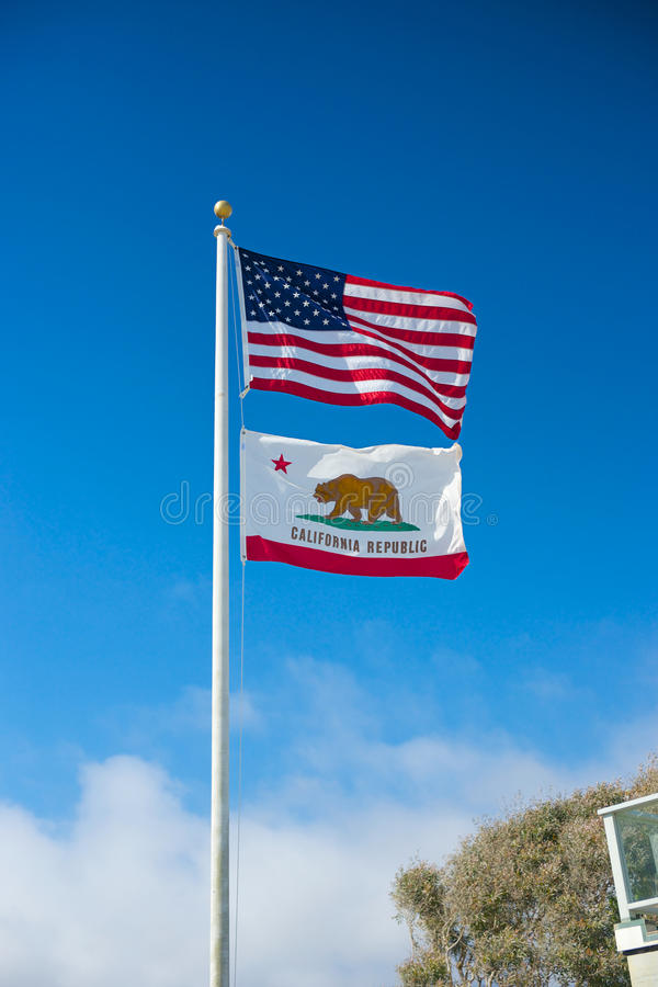 American and Californian Flag. American flag and Californian flag wave in the breeze under a bright blue sky royalty free stock photos
